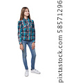 Teen girl in checkered shirt standing casually 58571296