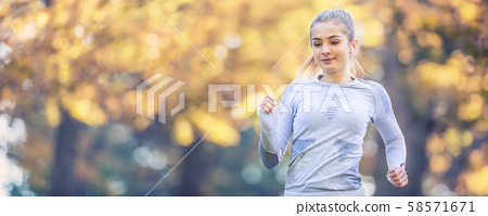 Runner woman in autumn park tree alley training in 58571671