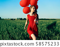 Freedom happy woman running with red balloons on green summer field 58575233