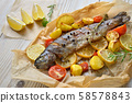 Baked lemon trout with oven-roasted rosemary potatoes and tomatoes, served on baking paper 58578843