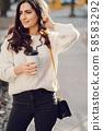 Cute brunette in a white sweater in a city 58583292