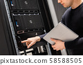 IT Support Holding Digital Tablet Examining and Perform Service on Servers 58588505