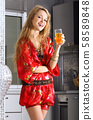 Happy woman in modern kitchen with glass of juice 58589848