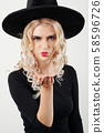Woman in witch costume blowing a kiss 58596726