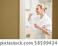 Happy woman brushing teeth 58599434