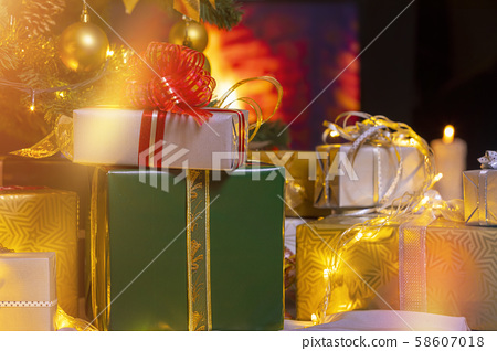Christmas presents and candles under Christmas tree 58607018