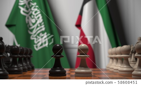 Flags of Saudi Arabia and Kuwait behind pawns on the chessboard. Chess game or political rivalry 58608451