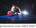 Female athlete playing ping pong on black 58623687