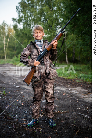 Father gave a son a shotgun rifle to carry. Happy boy prepared for hunding with his father together. 58623839
