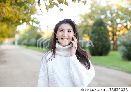 Asian smling girl wearing white sweater talking by smartphone and walking in park. 58635038