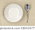 Empty soup bowl and silver spoon 58642677
