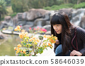 An Asian woman takes care of flowers in the Taichung Garden in Taiwan. 58646039