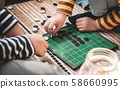 Closeup of kids hands playing reversi or othello traditional strategic board game by thinking, planing and use fingers flip the black reversible disc. Cognitive skills, Mind sport, Competitive concept 58660995