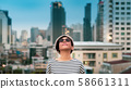 Stylish and smart look asian young woman stand alone on the rooftop building feeling satisfy and relaxing with the skyscraper urban scenic which has peaceful evening twilight. Modern city leisure. 58661311