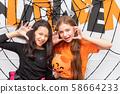 Happy girls standing front of Halloween party 58664233