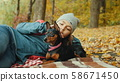 Girl relaxes in the autumn forest with her miniature pinscher 58671450