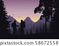 Two tourists walking through a mountain landscape 58672558