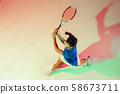 Young woman in blue shirt playing tennis in mixed light. Youth, flexibility, power and energy. 58673711