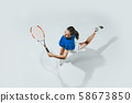 Young woman in blue shirt playing tennis. Youth, flexibility, power and energy. 58673850