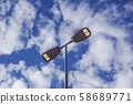 Three LED Street Lamps Affixed to an Iron Post Against a Deep Blue Sky 58689771