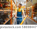 Builder with cart at the shelf in hardware store 58698447