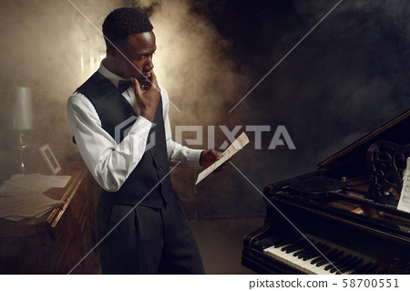 Black pianist with music notebook on the scene 58700551