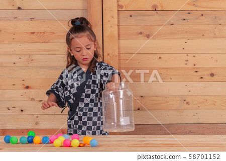 a boy playing colored ping pong balls in wooden 58701152