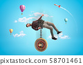 Man in casual clothes chained to roulette with hot air balloons and silver red space rocket in the 58701461
