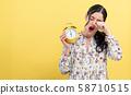 Yong woman holding a clock showing 6AM 58710515