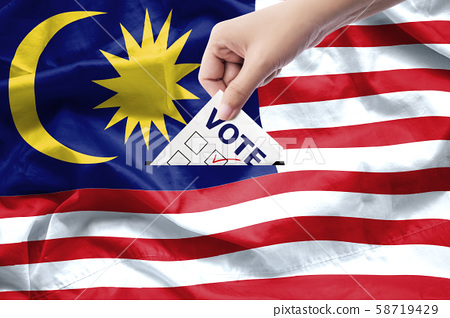 Malaysia general election concept. close up hand of a person casting a ballot at elections during voting on canvas Malaysia flag background. 58719429