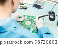 Technician soldering components to a PCB 58720803