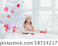Little girl in Santa hat writes letter to Santa near christmas tree in the cold winter morning. 58724217