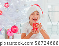 Handsome boy weared like mini Santa or elf is seating near the Christmas tree with a cup of hot 58724688