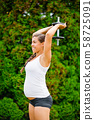 Pregnant Woman Performing Triceps Extension Exercise In Park 58725091