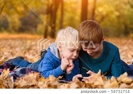 Two little brothers using smartphone, lying in 58732718
