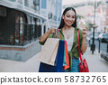 Happy Asian female taking payment card in the city 58732765
