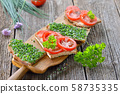 Vegetarian snack: Slices of buttered farmhouse bread with fresh chives and tomatoes 58735335