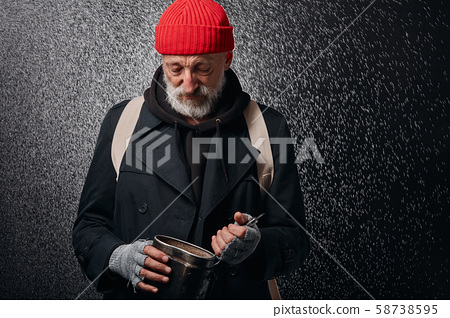 Sad homeless man trying to find some food in pan 58738595