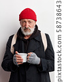 Old bearded beggar covering up in black wear holding mug of hot tea to warm himself in cold day 58738643