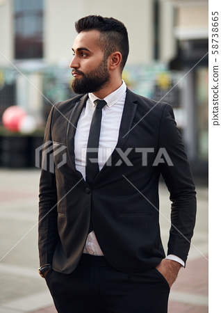 Young handsome businessman standing outdoor in formal clothes, tuxedo 58738665