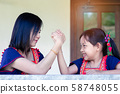 Asian daughter and mom arm wrestling having fight 58748055