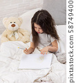 cute little girl drawing pictures while lying on bed 58749400