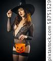 Sexy woman in lingerie holding Halloween pumpkin 58751529