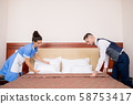 Young porter and chamber maid bending over bed while making it in the morning 58753417