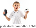 A little boy in a white shirt, blue shorts with blonde hair, black glasses with phone and card is 58753760