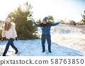 Loving couple play snowballs in winter in the 58763850