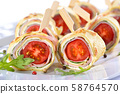 Finger food: Rolls of thin pancakes (crepes) with ham, cream cheese,rocket salad and cherry tomatoes 58764570
