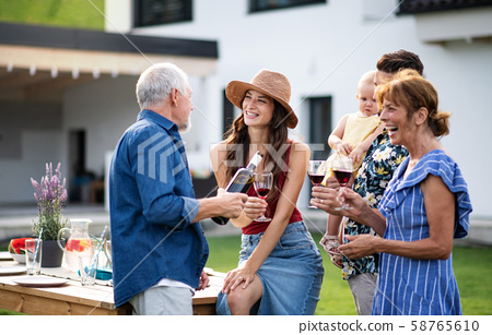 Portrait of people with wine outdoors on family garden barbecue. 58765610