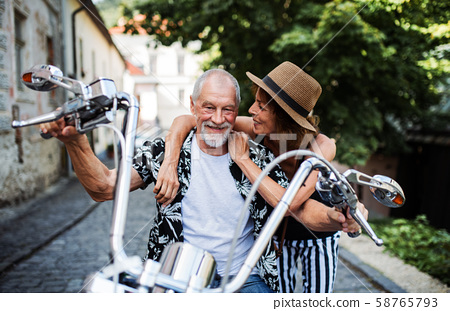 A cheerful senior couple travellers with motorbike in town. 58765793