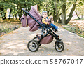 Portrait of little cute toddler girl sitting in stroller or pram and going for a walk. Happy cute 58767047